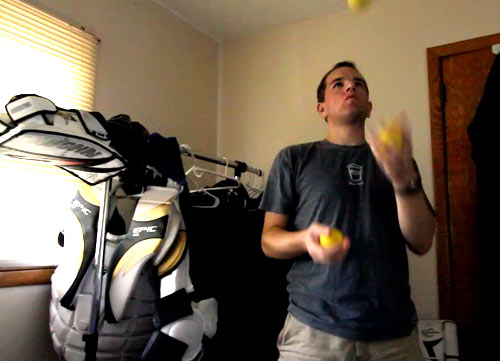 Juggling lacrosse balls with my goalie gear in the background